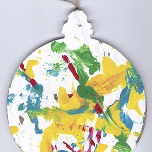 An abstract acrylic painting on a wooden ornament with green, yellow, blue, and red streaks and dots