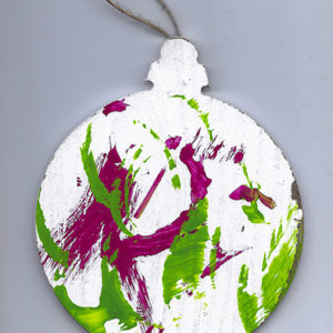 An abstract acrylic painting on a wooden ornament with red and green streaks and dots